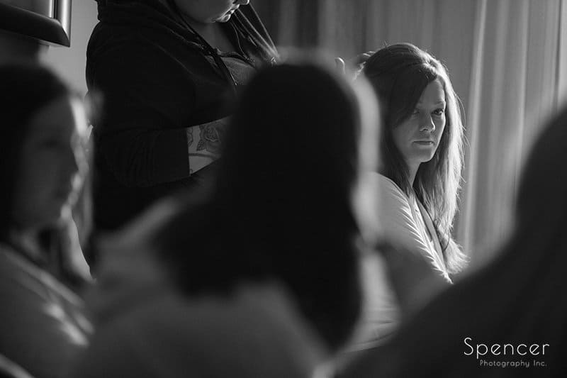 bride looking at her bridesmaids as she gets ready
