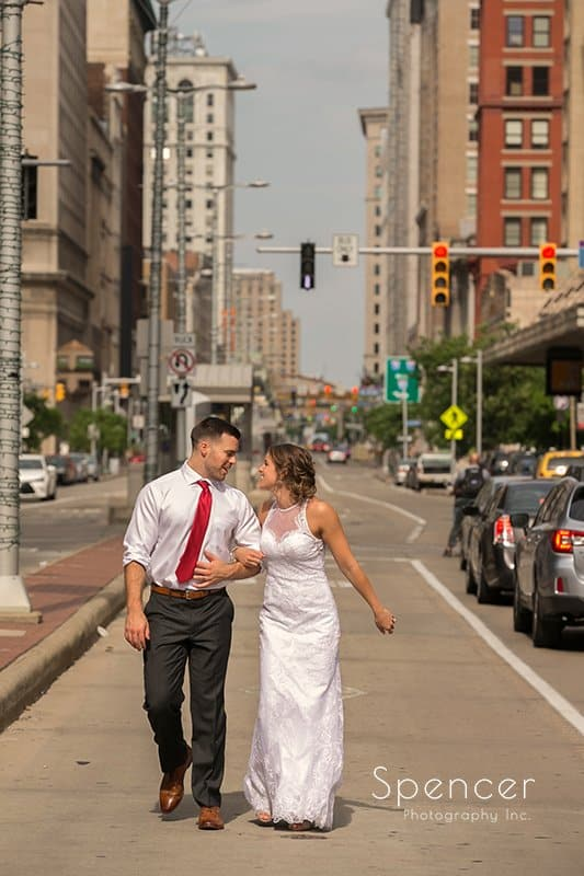 bride and groom walking down street in downtown Cleveland