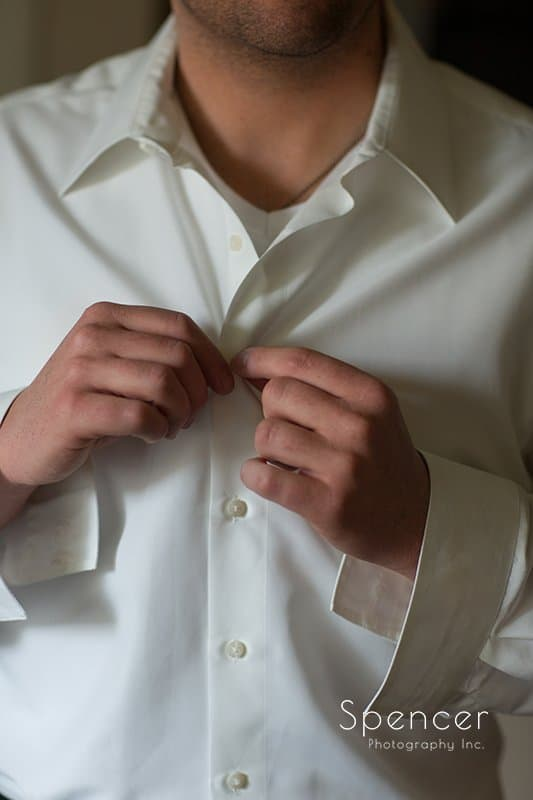 groom buttoning up his shirt
