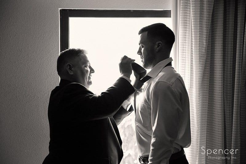 grooms dad helping him prepare for wedding