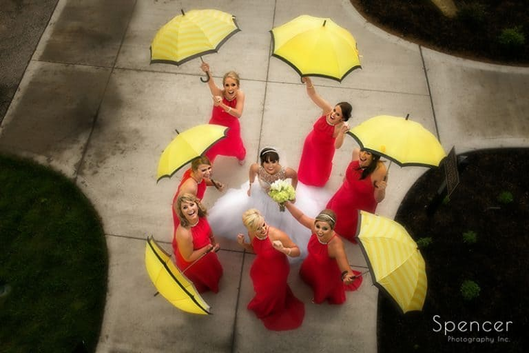 bridesmaids lauging with umbrellas in wedding picture at Firestone