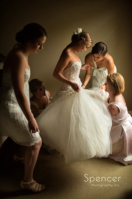 bride putting on her wedding dress