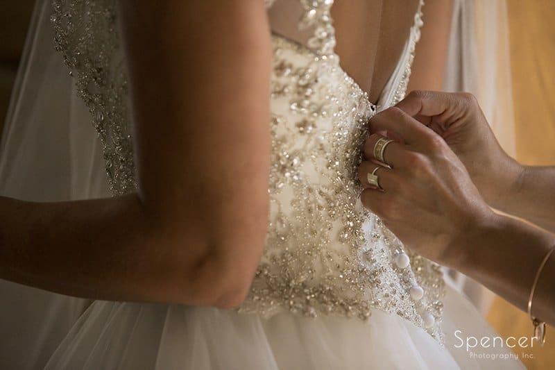 11 close of of bridesmaid buttoning wedding dress