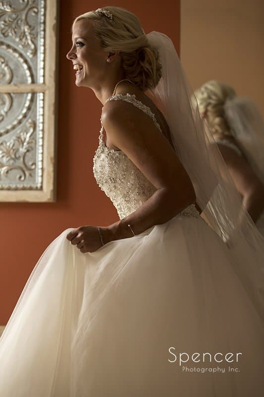 bride smiling while holding wedding dress