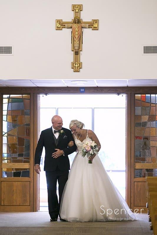 bride walking down wedding at aisle at St. Barnabas