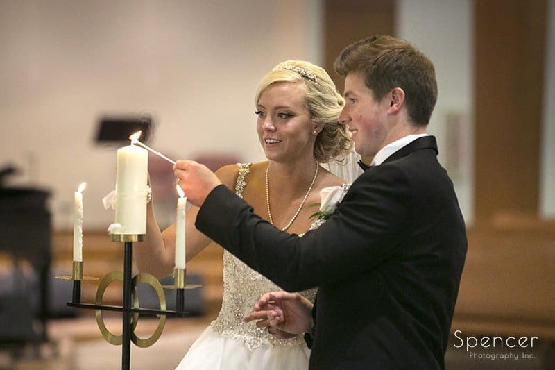 bride and groom lighting unity candle at st barnabas