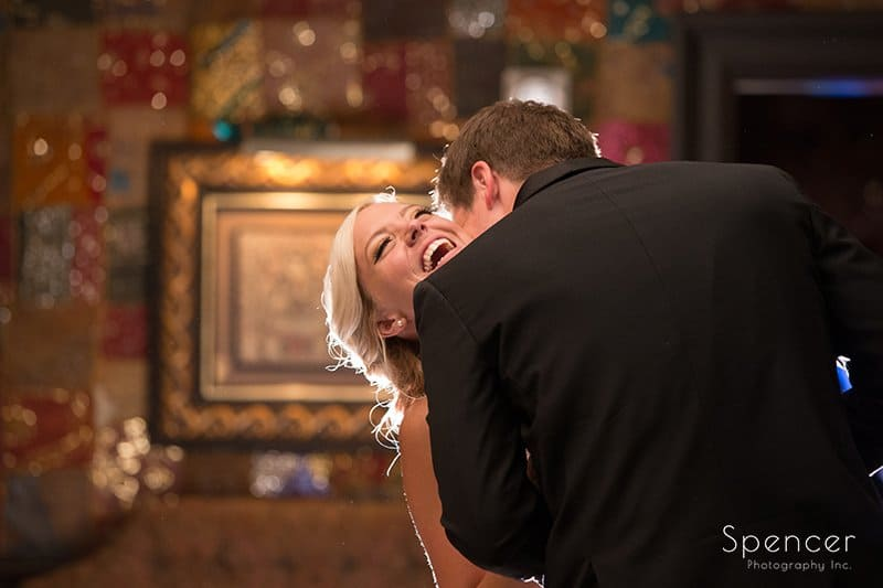 bride laughing while groom kisses her at House of Blues Cleveland