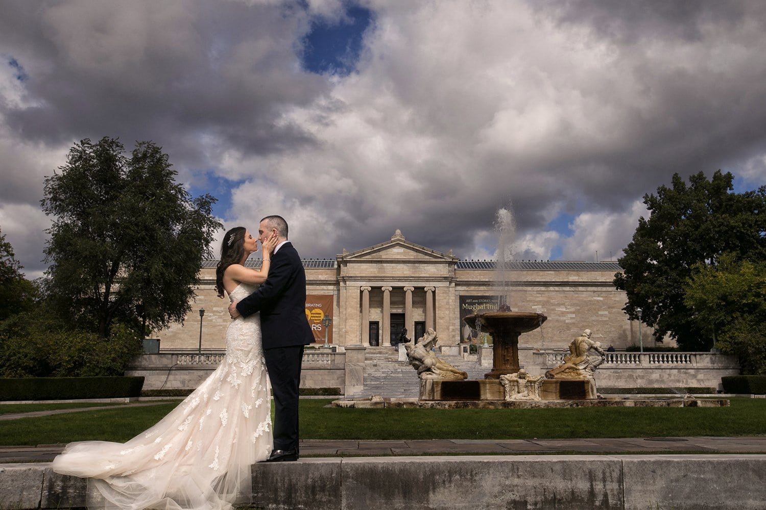 bride kissing groom in front of Cleveland Museum of Art