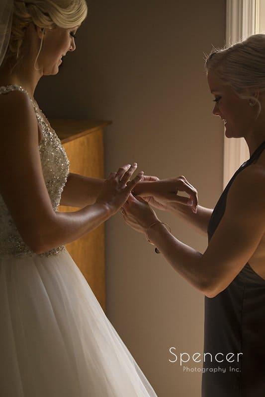 bridesmaid putting on brides wedding day bracelet