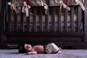 cleveland newborn baby laying in front of crib