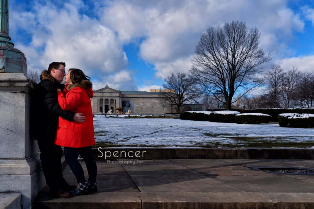 couple kissing in engagement pictures in front of Cleveland Museum of Art