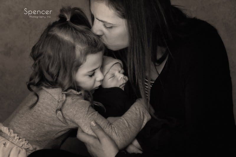 mom holding newborn baby kissing her toddler in Cleveland