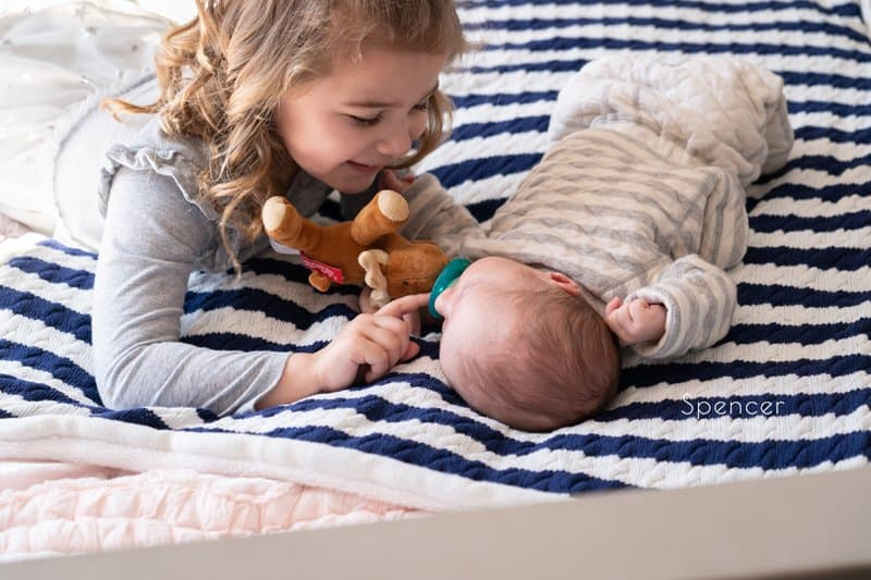 toddler playing with newborn brother