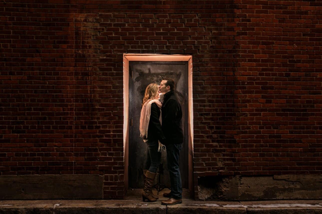 man kissing woman in engagment picture behind cleveland house of blues