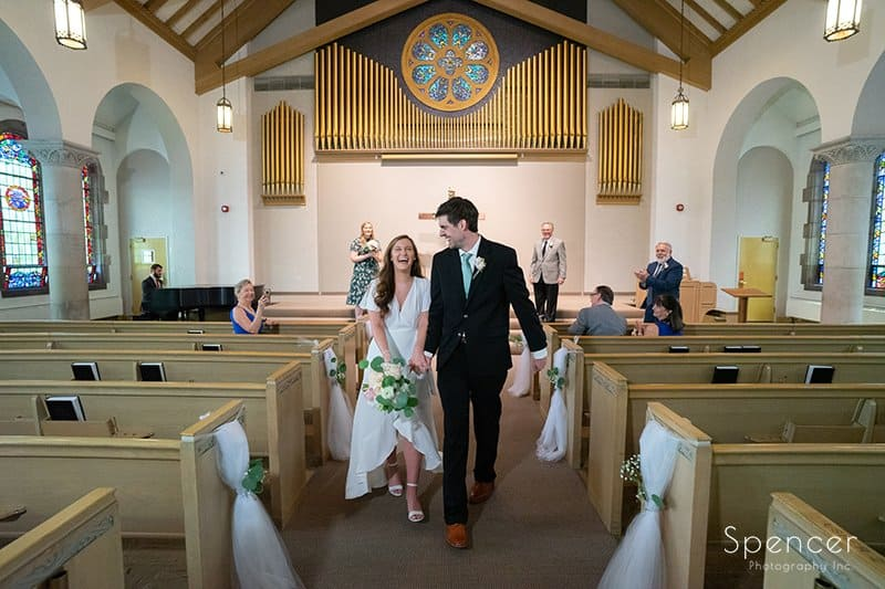 bride and groom exit their wedding ceremony at The Chapel in Akron