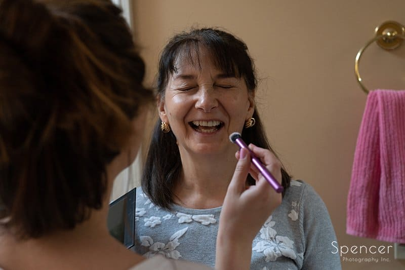 mom laughing as bride applies wedding day make-up