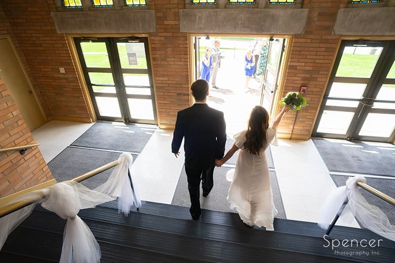 bride and groom walking out of wedding at The Chapel in Akron