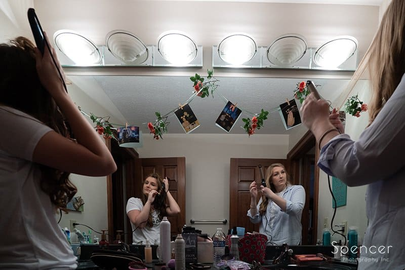 bride and maid of honor prepping for wedding day