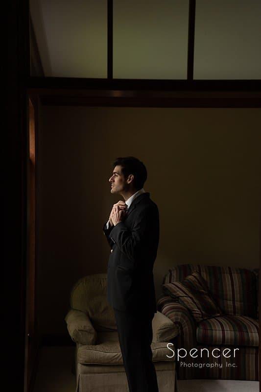 groom adjusting his wedding tux tie