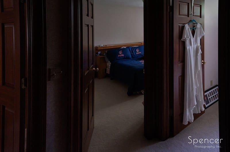 brides wedding dress hanging on door