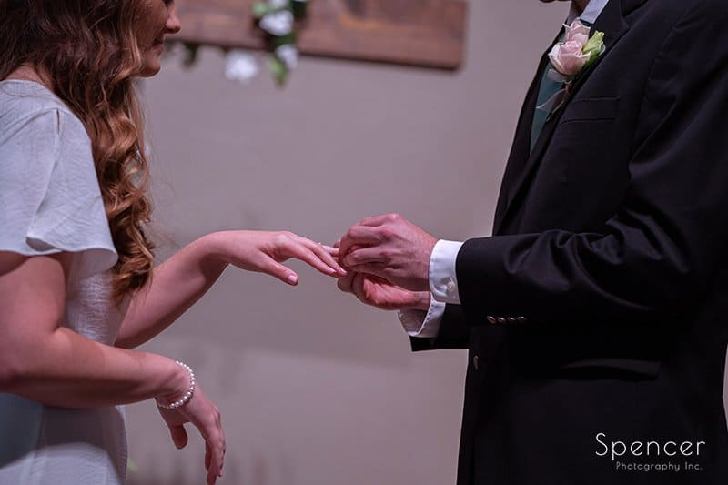 groom putting on wedding ring at wedding ceremony