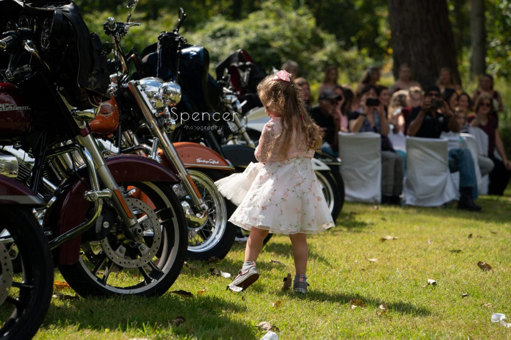 a little flower girl during outdoor wedding ceremony