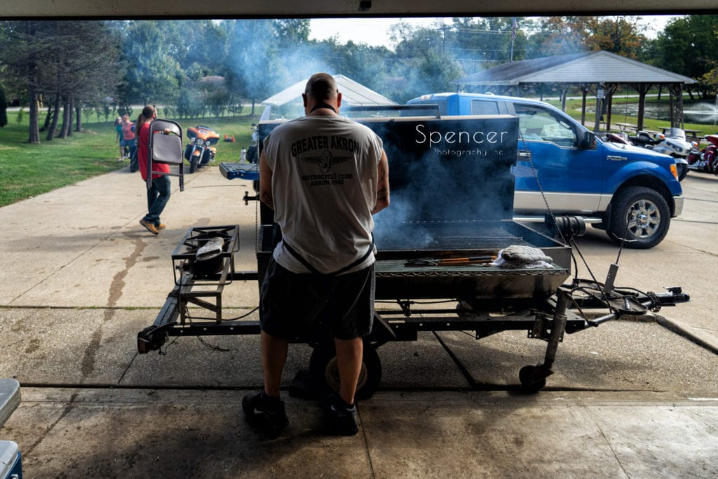 man prepping barbeque for merriman valley wedding
