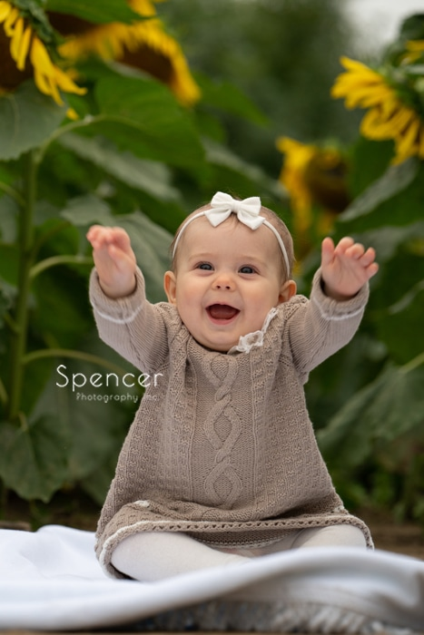 baby waving arms in picture in sunflower field