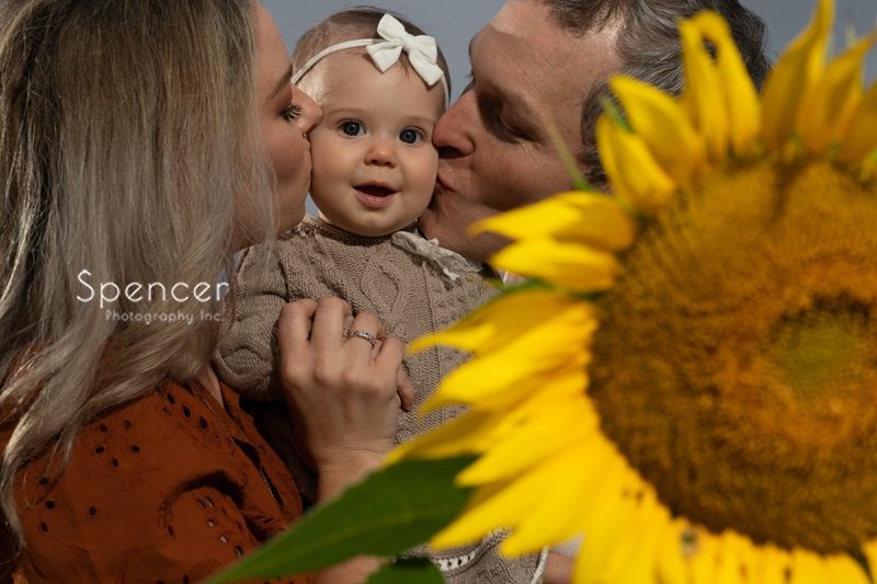parents kissing baby in picture in sunflower field