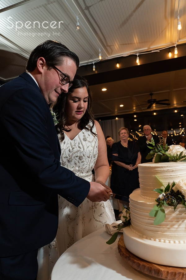 bride and groom cutting wedding cake at The Club at Hillbrook