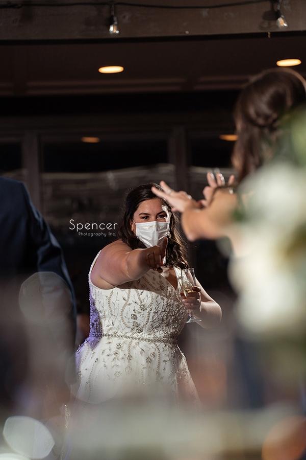bride making hand gestures at her wedding reception