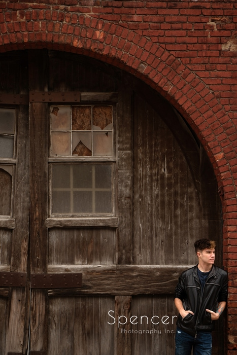 Senior picture of boy leaning on brick wall