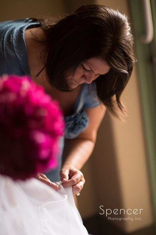 mom helping bride with wedding dress at Troon North