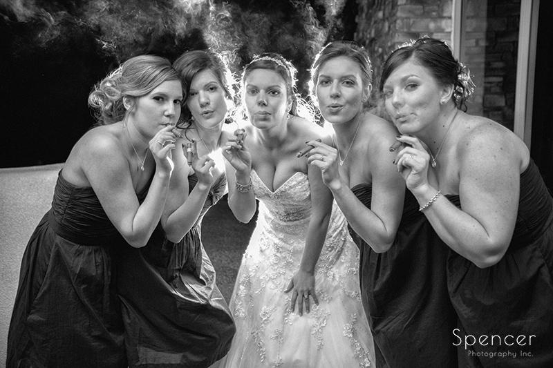 bride and bridesmaids smoking cigars at Troon North wedding reception