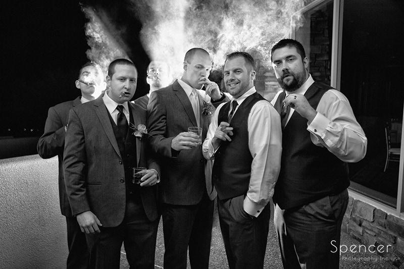 groom and groomsmen smoking cigars at wedding reception at Troon North