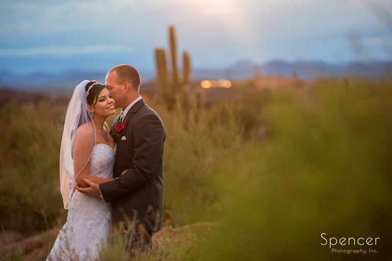 groom kissing brides ear outside of their wedding reception in Scottsdale Arizona