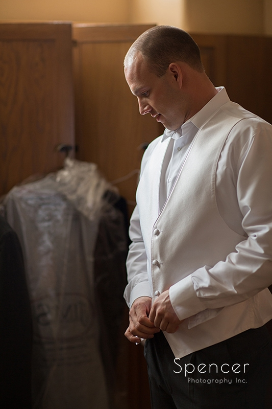groom buttoning shirt before wedding at Troon North Golf Club