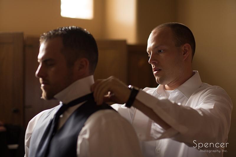 groom helping best man get dressed at Troon North