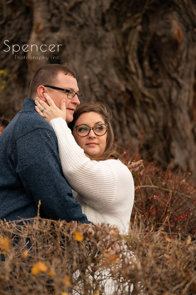 bride touching grooms face in engagement pictures at Wade Oval