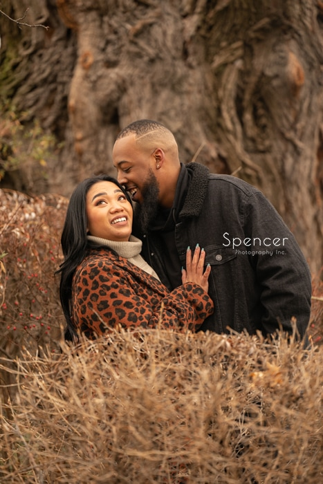 man kissing woman in Wade Oval Park engagement picture