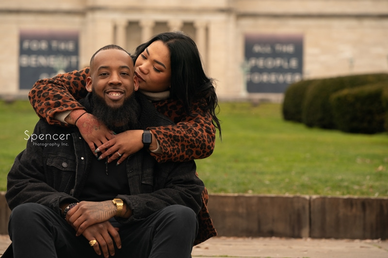 woman hugging man in engagement photo at Cleveland Museum of Art