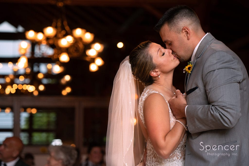 bride and groom kissing at their wedding reception at Rolling Acres Golf Course