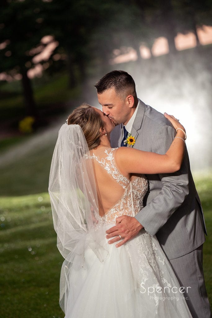 bride and groom kissing on course at Rolling Acres Golf Course