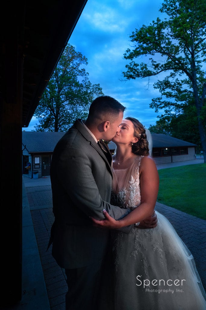 bride and groom kissing outside of reception at Rolling Acres Golf Course