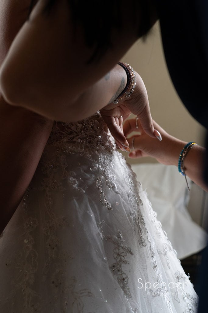 maid of honor helping bride with wedding dress