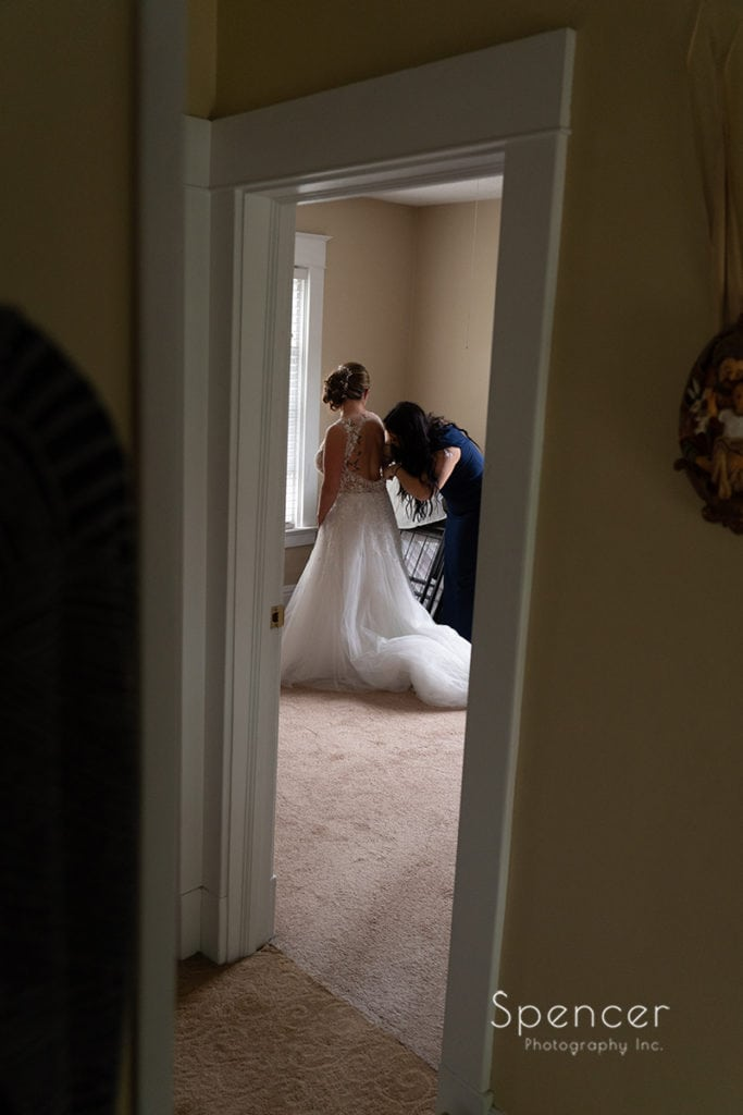 bride putting on wedding dress with maid of honor