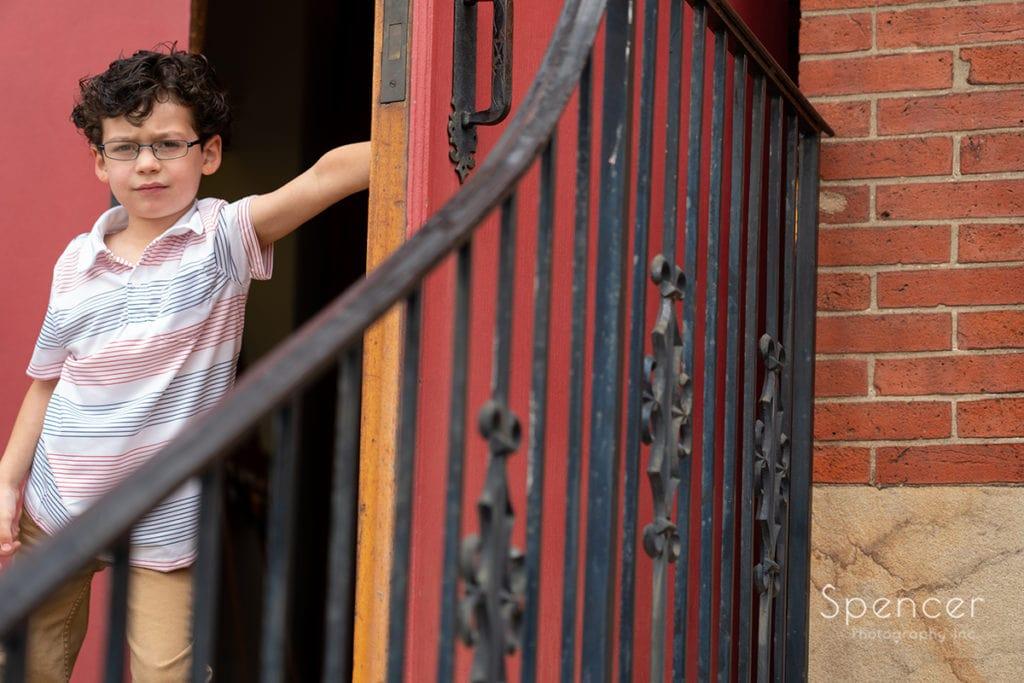 little boy holding open door at church