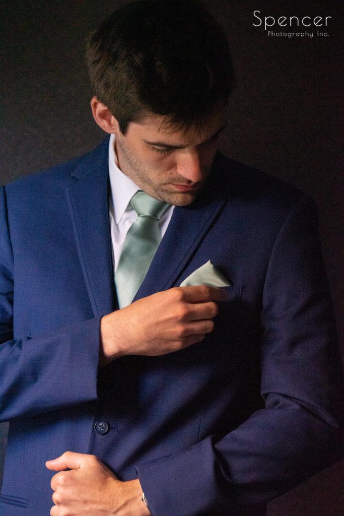 groom adjusting his pocket square