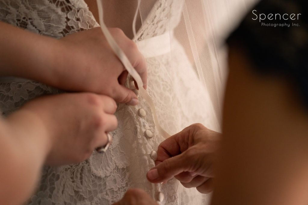 maid of honor helping mom with wedding dress