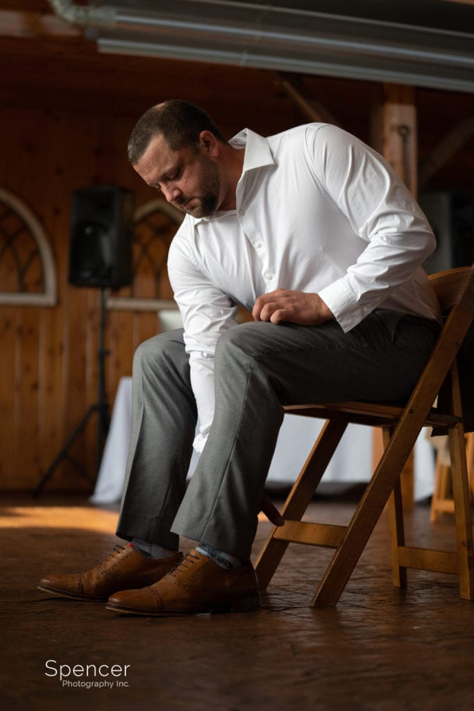 groom putting on wedding shoes at Parker Barn